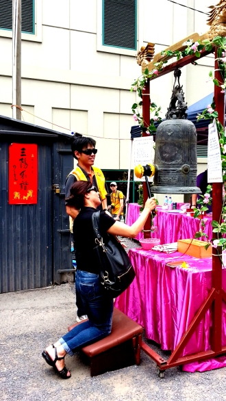 Anglo-Australian woman rings a Buddhist bell at the Lunar Festival, Melbourne, 2015