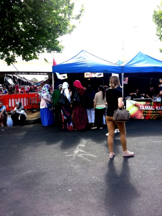 Women visit a food stall at the Malaysian Street Festival 2014