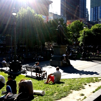 People lay in the sun outside the Melbourne Library