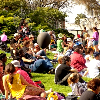 Families sit on the grass during the Wominjeka Festival 2015