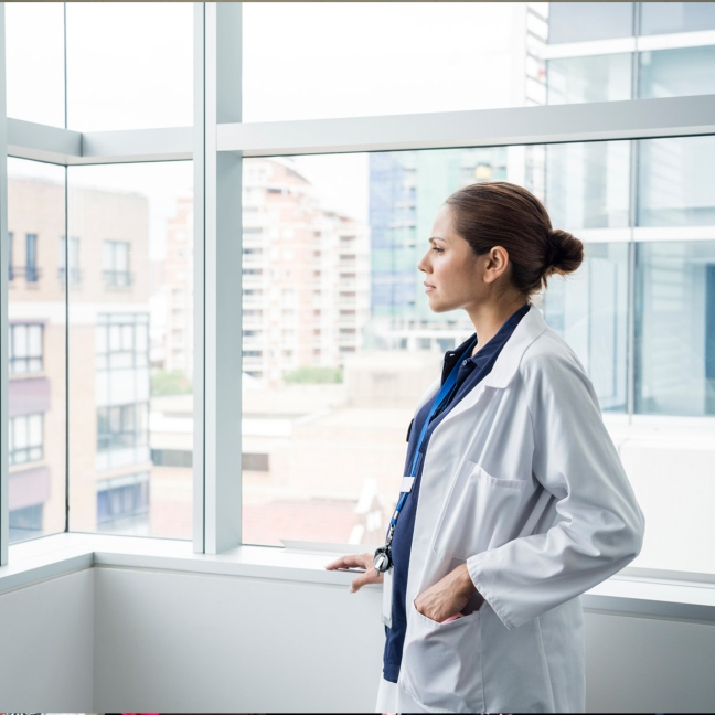 Aboriginal woman medical doctor stares out of a large window