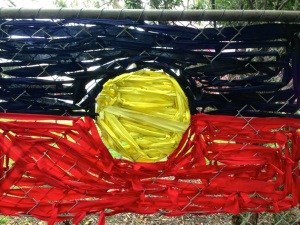Aboriginal flag drawn over a fence