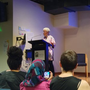 Professor Patricia Hill Collins speaks at a podium at the front of a room
