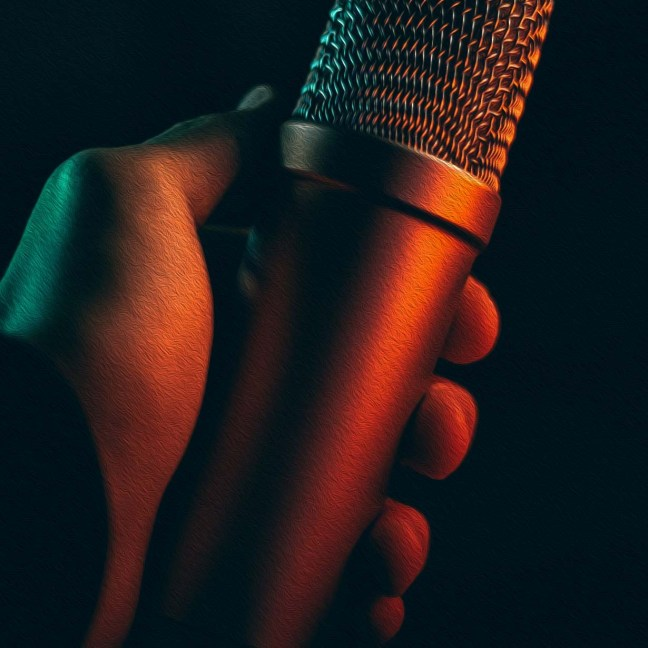 A dark-skinned hand holds out a microphone against a dark background