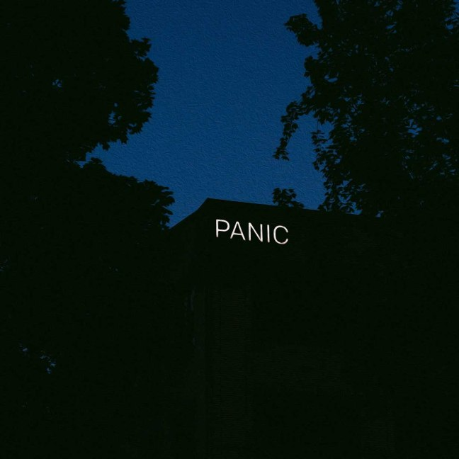 A large building at dusk is obscrured by trees and darkness. A lit sign says: PANIC